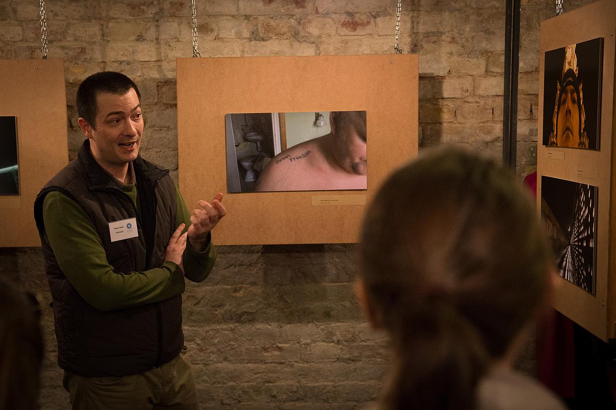 Dobos Péter a kiállításmegnyitón, háttérben a képei
