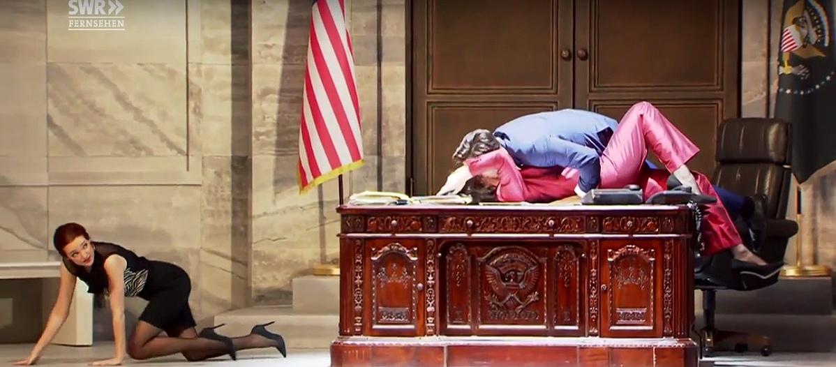 Hillary Clinton beugrik egy csókra, Monica kúszva menekül az asztal alól a Badisches Staatstheater színpadán