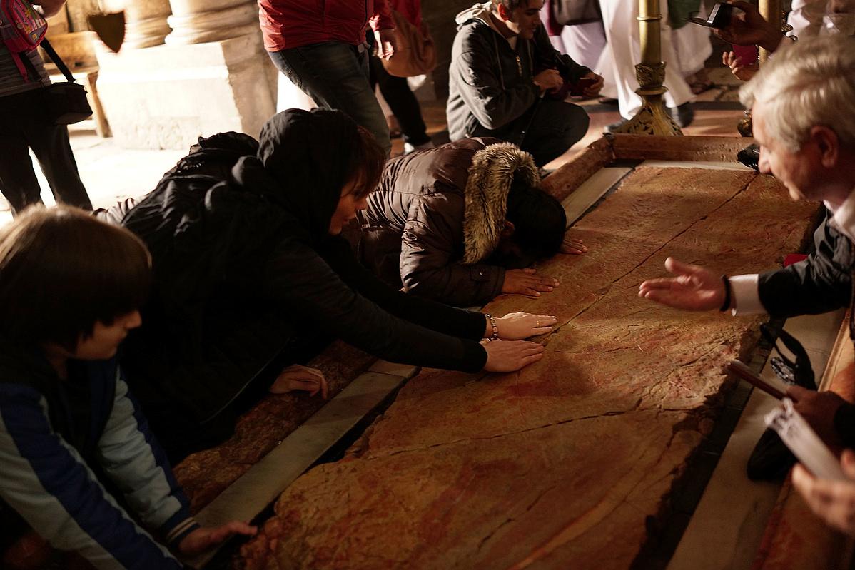 Zarándokok csókolják a márványlapot a Szent Sír-templomban