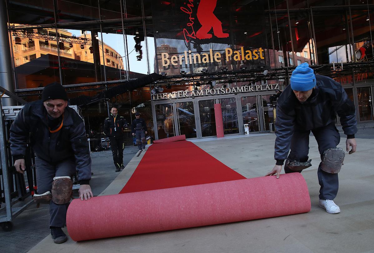Munkások vörös szőnyeget terítenek le a Berlinale fő helyszínénél